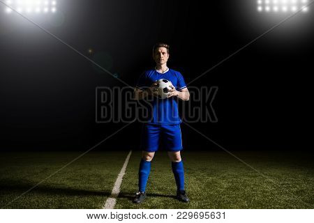 Full Length Of Professional Male Soccer Player In Blue Uniform Standing On The Pitch Holding A Ball
