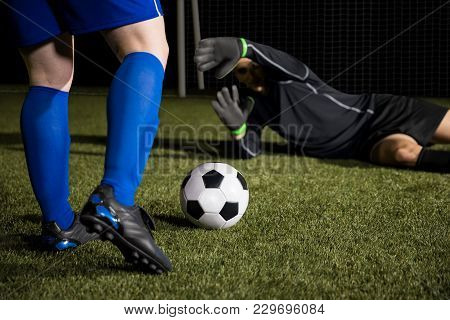 Legs Of A Footballer Player Kicking The Ball And Diving Goalie Trying To Save The Goal