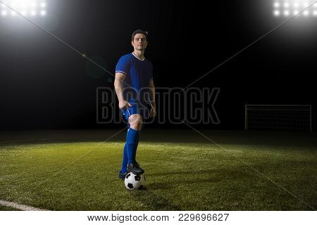 Full Length Portrait Of Professional Young Football Player In Blue Uniform Standing On Football Pitc