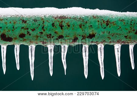 Frozen Icy Down Pipe, Icicles On Green Background