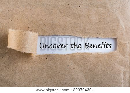 Uncover The Benefits Text On Brown Envelope. Word Uncover The Benefits On Torn Paper. Concept Image.