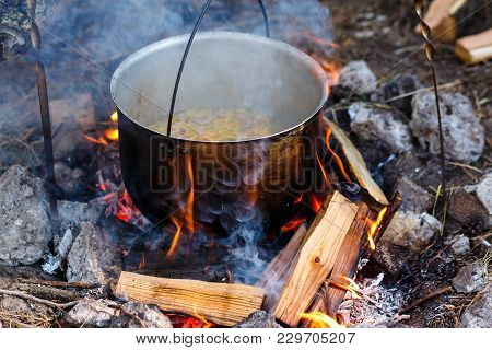 Iron Pot With Food On A Burning Fire. Food In A Metal Cauldron Is Cooked On Fire. Cooking Food In Na