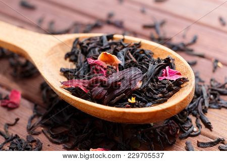 Composition Of Natural Tea With A Leaves Of Rose. Macro Photo Of Tea Petals On A Wooden Spoon With A