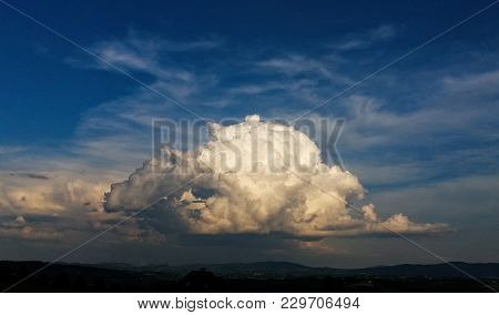 Storm Cloud Over The Countryside. Cloud Illuminated By Sun. Blue Sky Above.