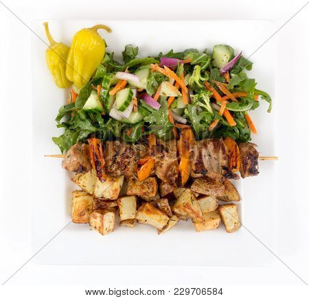Pork Kebab Skewer Dish With Potatoes And Salad Over White Background