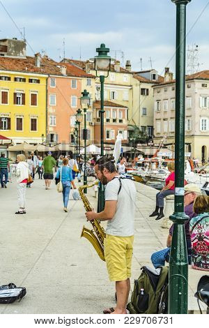 Rovinj, Croatia, September 27, 2017: Street Artist Playing Music With A Saxophone, Tourist Give Mone