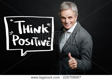 Think Positive. Emotional Enthusiastic Confident Senior Man Standing With His Thumb Up And Smiling C