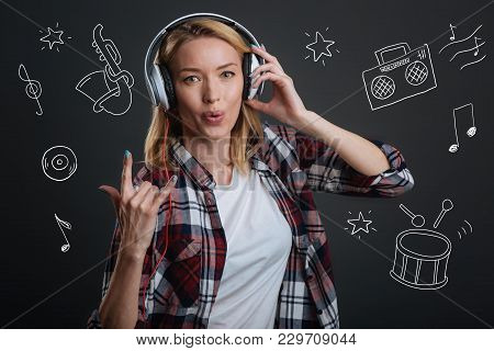 Enjoying Music. Cheerful Emotional Young Woman Showing A Goat Gesture While Standing Alone With Big