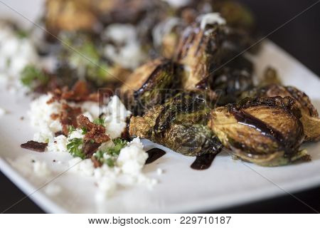 An Appetizer Plate Of Roasted Brussels Sprouts Garnished With Feta Cheese And Bacon, With A Drizzle