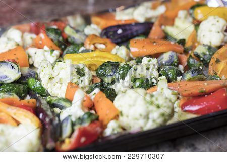 Foiled Lined Baking Sheet Filled With Raw Carrots, Cauliflower, Brussels Sprouts, Baby Bell Peppers