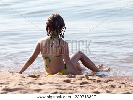 Little Girl In A Bathing Suit On The Beach .