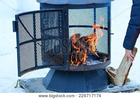 Fireplace In Winter Season Charged With Firewood, In The Burning Process. Wood-burning Fire Pit With