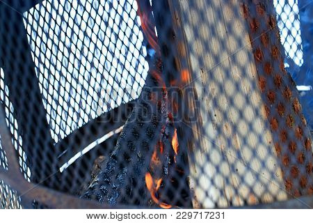 Outdoor Chimney With Steel Grille And Firewood In The Burning Process. Outdoor Metallic Fireplace In