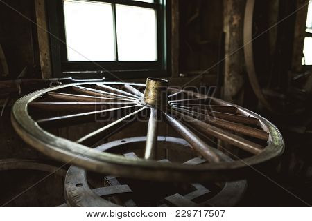Old Wooden Wheel Of The Horse Cart In The Ancient Forge. The Old Car Wheel Is Considered To Be The S