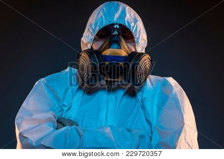 Quarantine, virus infection concept. Man in protective suit and antigas mask with glasses. Ebola, toxic gases, biological warfare, infections and diseases