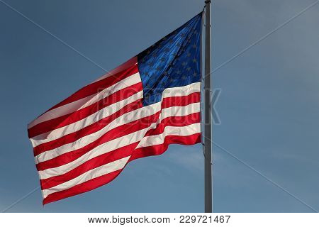 American Flag Billowing In The Wind Against A Blue Sky