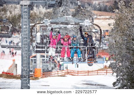 happy people are lifting on ski-lift for skiing in the mountains