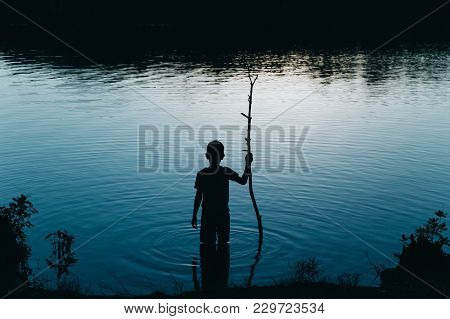 Boy Standing In The River At Night. Kid With A Stick Comes Into The Water In The Dark. Copy Space Fo
