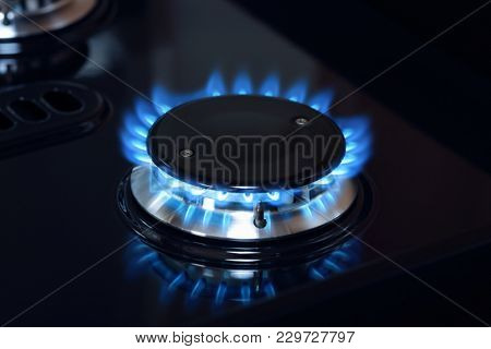 Natural gas burner flame on black stove
