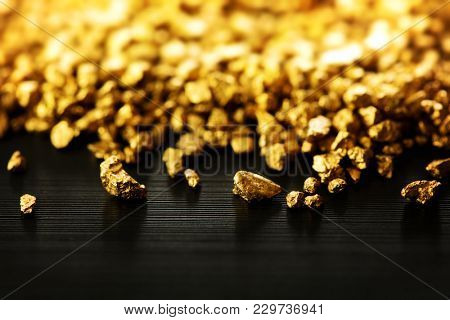 Gold nuggets spilling out on black table or surface. wealth power and commerace concept image.