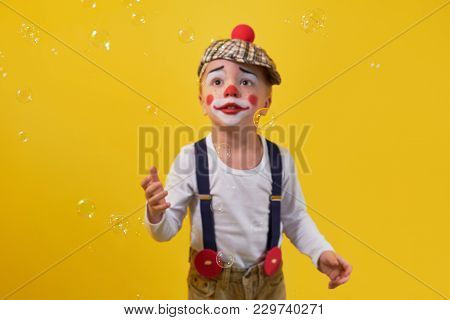 Cute Little Boy Clown In A Costume, Makeup, Catches Hands Bubbles, Soft Focus. Kid On The Bright Yel
