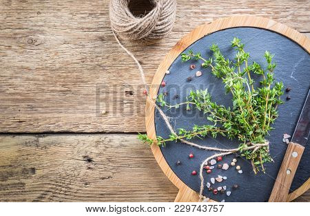 Close Up View Of Thyme Bunch Tied Twine On Rustic Background. Top View With Copy Space.