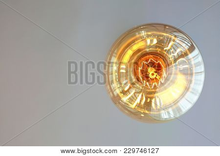 Bottom View Of Sphere Vintage Filament Lamp Hanging From The White Ceiling With Reflection On The Su