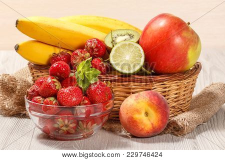 Fresh Strawberries, Nectarine, Lime, Kiwi, Banana, Apple In A Wicker Basket On A Wooden Table. Set O
