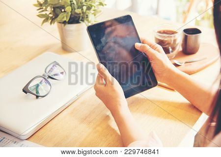 Beautiful Business Working Woman Using Ipad While Working With Laptop And Reading Report , Graphs ,