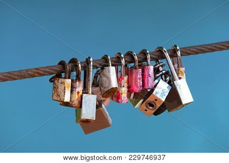 Row Of Old Rusty Lock On The Sling Wire With Blue Sky Background On Believe Of Forever Love
