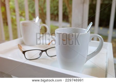 Stained Used White Cup Of Coffee On Square Table With A Glasses With Soft Morning Light