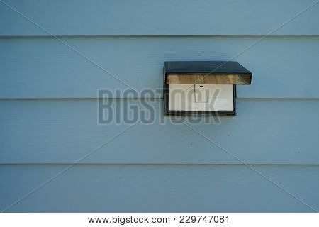 Bell Switch With Rain Cover On The Pastel Light Blue Wooden Wall In Front Of House