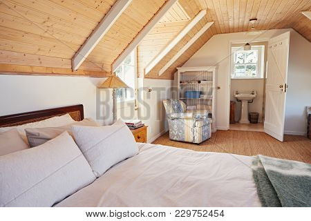 Interior Of A Comfortable Master Bedroom With An En Suite Bathroom In The Loft Of A Contemporary Res