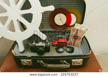 Part Of Leather Travel Valises Or Old Suitcase With Camera, Toy Car, Vintage Vinyl Record And Black