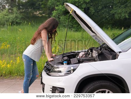 Girl Examining Her Broken Car On The Country Road. Young Brunette Woman Trying To Repair Her Broken