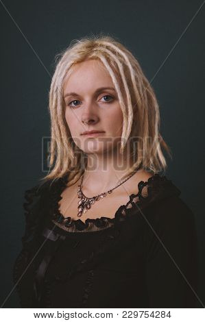 Retro Style Portrait Of A Young Woman With Blond Dreadlocks And Vintage Blouse And Necklace