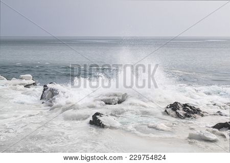 The Sea Shore Is Ice-cold And Snow-covered Coastline And Strong Waves, Splashes Into The Sky. Far Ea