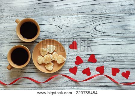 On A Wooden Background There Are Two Cups Of Coffee Next To A Saucer With Cookies In The Form Of Hea