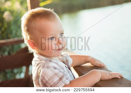Beautiful Boy Baby Leaning On Railing Of Bridge Looking At Water