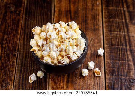 A Bowl With Seductive Popcorn On A Wooden Background.