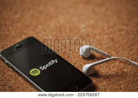 Malaga, Spain - March 5, 2018: Mobile Phone With Spotify Logo In The Screen And White Earphones, Pla