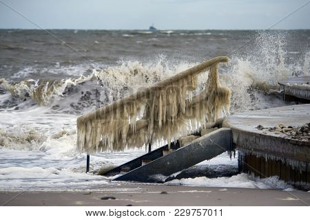 Huge Ice Icicles On Wooden Bridge Handrails. Danish Beach In A Winter Eastern Storm.