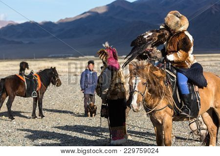 SAGSAY, MONGOLIA - SEP 28, 2017: Kazakh Eagle Hunter (Berkutchi) with horse teaches his daughter to hunting to the hare with a golden eagles in the mountains of Bayan-Olgii aimag.