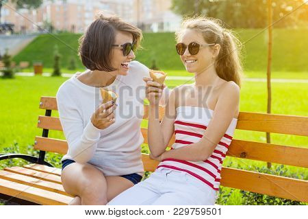 Holiday With The Family. Happy Young Mother And Cute Daughter Teenager In City Park Eating Ice Cream