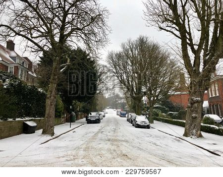 HAMPSTEAD, LONDON - MARCH 1, 2018: Snow covers parked cars in a quiet residential street during Storm Emma, also named the 'Beast from the East', in suburban Hampstead, North London, UK.