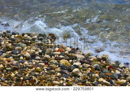 Bright Colorful Stones On The Beach With Clear Clear Water In Mediterranean Sea. Focus Runs Through