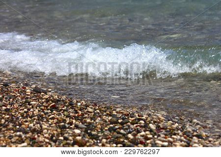 Bright Colorful Stones On The Beach With Clear Clear Water, Foamy Wave. Focus Runs Through The Middl