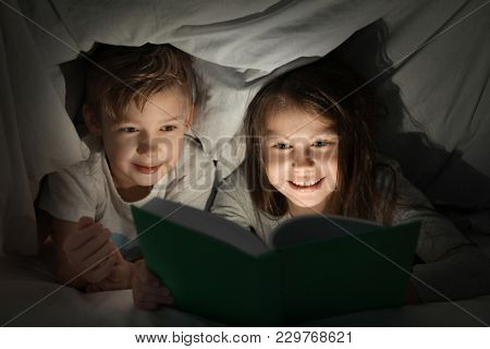 Cute little brother and sister reading bedtime story under blanket in evening