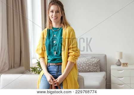 Young woman in yellow cardigan indoors