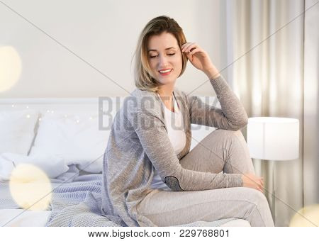 Young woman in warm cardigan at home
